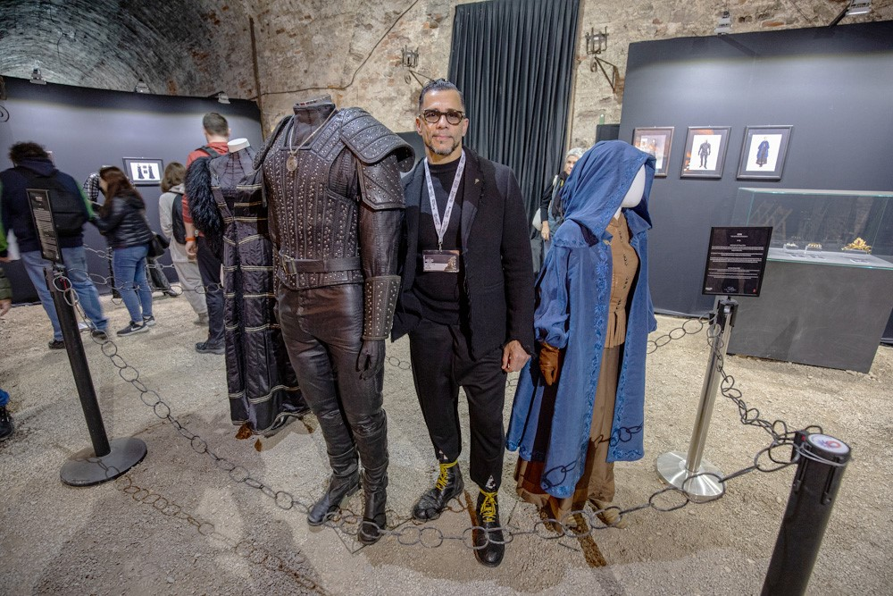 Тим Аслам позирует возле брони Геральта на выставке в Италии